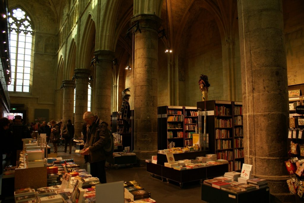A picture of a bookstore situated in the interior of an old gothic church. This illustrates broad attention while waiting in the bookstore.